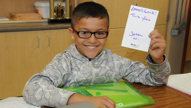 Holdeman Elementary School fourth-grader Chris Lopez receives his homework pack, complete with a note of encouragement from a LifeLock volunteer.