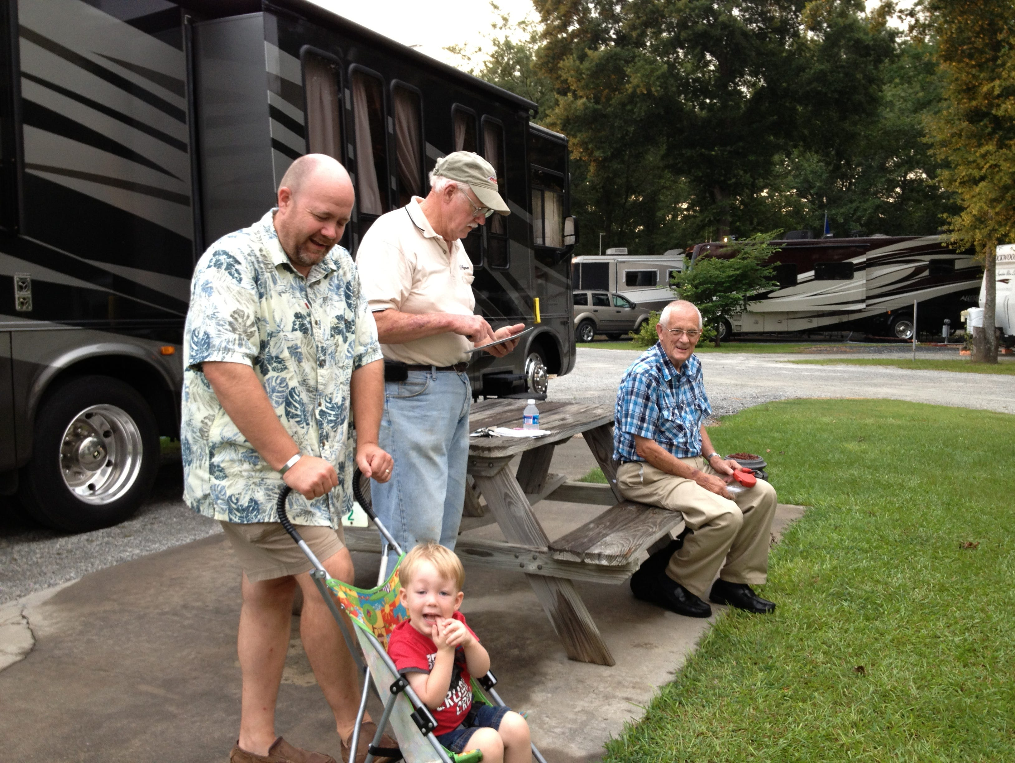 Twin Oaks guests, from left to right: Andy Schneider and his son Caleb (in the stroller), John Newham (using an iPad to find the missing owner's manual for O'Donnell's RV), and Ernie Gaines.