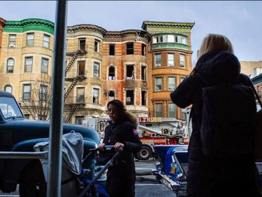 Neighbors look over a burned out building, the scene