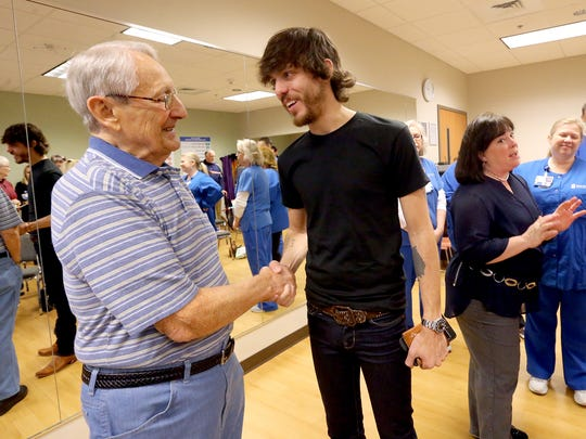 Ray Fairbanks, left, gets a chance to talk with country music artist Chris Janson after Janson spoke with a group of COPD patients on Wednesday, March 9, 2016, about how he learned to breathe better when he learned to play the harmonica.