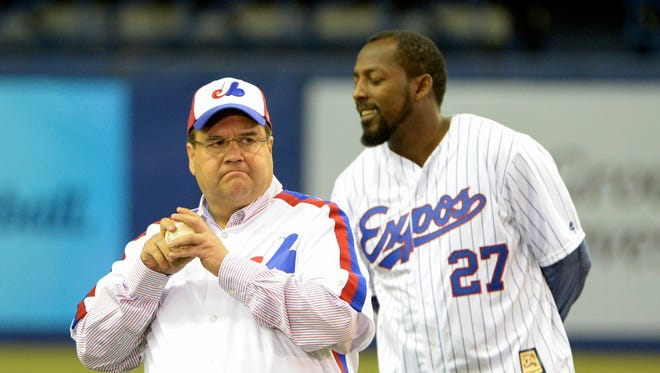 Montreal mayor Denis Coderre throws the first pitch as former Expos Vladimir Guerrero looks on before the game between the Cincinnati Reds and the Toronto Blue Jays at the Olympic Stadium.