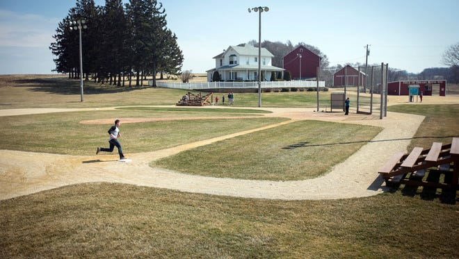 """In this April 12, 2014 photo, Matt Gallowic stopped by the Field of Dreams on the way to a wedding and rounded the bases near Dyersville, Iowa. """"Field of Dreams,"""" which premiered in Iowa 25 years ago, has become one of the most beloved movies in a generation and transformed this small patch of Dubuque County into Iowa's most famous farm."""