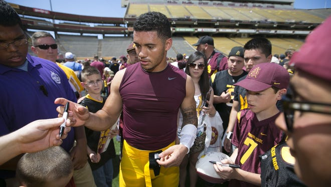 ASU running back D.J. Foster signs autographs for fans following the ASU football spring game at Sun Devil Stadium in Tempe on Saturday, April 19, 2014.