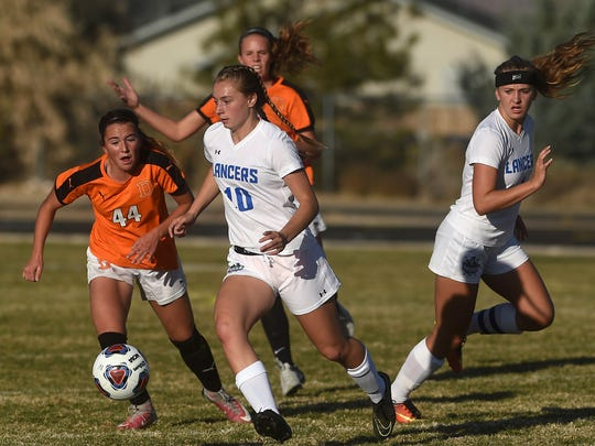 McQueen's Kendra McAninch (10) battles Douglas' Peri Buck (44) for the ball during their soccer game at Spanish Springs High School on Nov. 1.