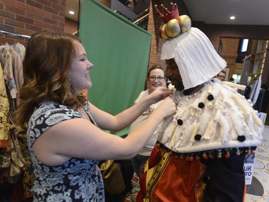 Antoine Batiste, II, gets a hand putting on a costume from Alice in Wonderland before having photos made during the Business After Hours at the Alabama Shakespeare Festival in Montgomery on February 26, 2015.