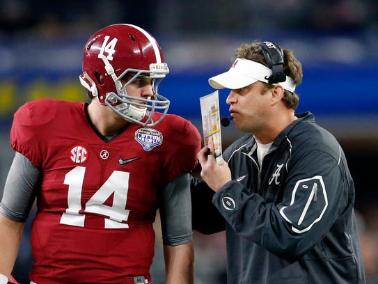 Alabama quarterback Jake Coker talks with offensive
