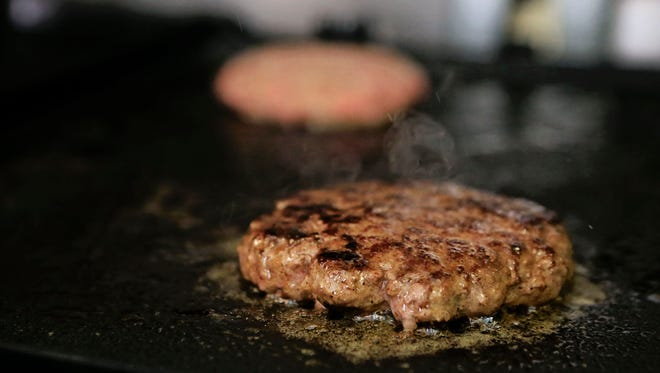 A hand-shaped hamburger pattie sizzles on a grill at Coqui's Cafe in downtown New Albany at the corner of Bank and East Market Street.  By Matt Stone, The C-J May 29, 2015