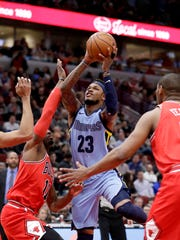 Memphis Grizzlies' Ben McLemore, center, shoots between Chicago Bulls' David Nwaba, left, and Cristiano Felicio, right, during the first half of an NBA basketball game Wednesday, March 7, 2018, in Chicago. (AP Photo/Charles Rex Arbogast)