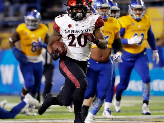 FILE - In this Saturday, Nov. 4, 2017 file photo, San Diego State running back Rashaad Penny runs against San Jose State during an NCAA college football game in San Jose, Calif. Two of college football's most dominant rushing attacks will clash when San Diego State faces Army in the Armed Forces Bowl on Saturday, Dec. 23, 2017, even though the two offenses are dramatically different.(AP Photo/Marcio Jose Sanchez, File)
