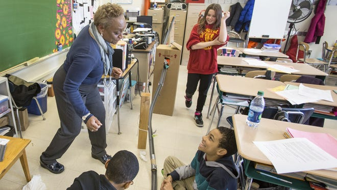 Fifth-grade teacher Vanessa Preston advises her then-10-year-old students Garrett Gaskins (left), Ilyas Tillman (right) and Kara Smith on how to improve their marble roller coaster during science lessons at Mount Pleasant Elementary School in 2014.