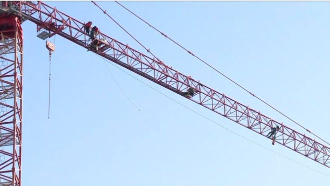 At least seven protesters have climbed a construction crane in northwest D.C. in response to President Donald Trump.