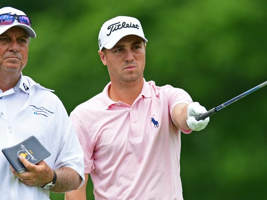 Justin Thomas, right, and his caddie, Jimmy Johnson, examine the fair way on the 18th hole during the third round of the Memorial golf tournament Saturday, June 2, 2018, in Dublin, Ohio. (AP Photo/David Dermer)