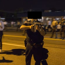 A St. Ann, Missouri, police officer points an assault rifle at a protester of the death of teenager Michael Brown August 19, 2014 in Ferguson, Missouri.