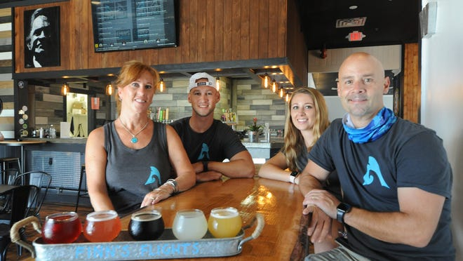 Dave and Kathi DeMinico have opened up Finn's Craft Beer Tap House with some sweat equity from their children, Brody DeMinico , second from left, and Marena DeMinico, second from right.                                                                                                                                                                                                                                                                                                                                                                                                                                                                                                                                                                               The restaurant, which has a grand opening at 4:30 p..m. Friday, features 32 taps of locally brewed craft beers, seltzers and cider on tap.