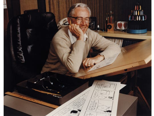 Charles M. Schulz sitting at his drawing board in his