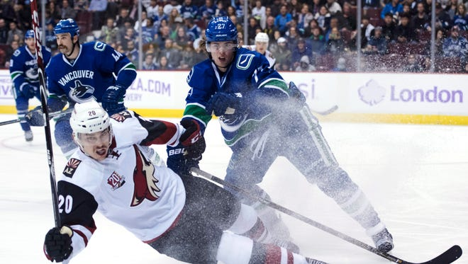 Vancouver Canucks defenseman Ben Hutton (27) fights for control of the puck with Arizona Coyotes center Dylan Strome (20) during the first period of an NHL hockey game Thursday, Nov. 17, 2016, in Vancouver, British Columbia. (Jonathan Hayward/The Canadian Press via AP)