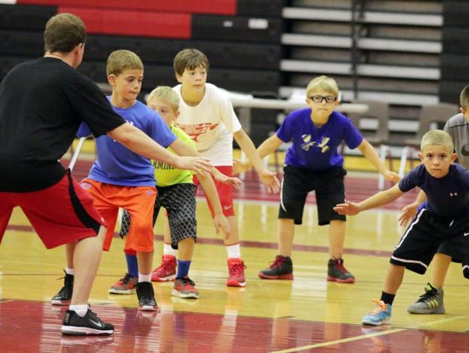 Youngsters learn the fundamentals of defense at the Hoop-Stars Youth Basketball Camp under the direction of Aubrey Kooistra, far left, Monday June 23, 2014 at Sheboygan South.