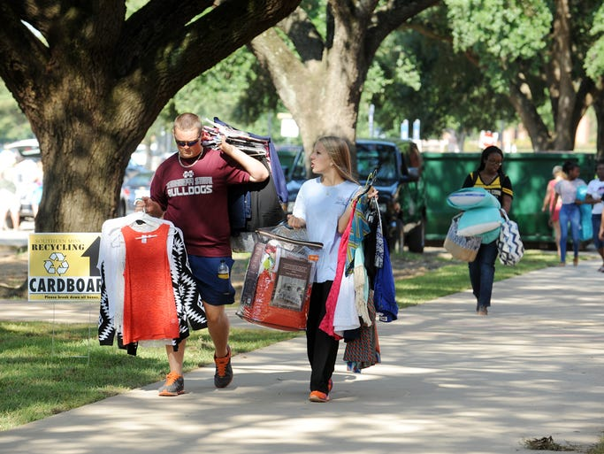 Jake Lindgren, left, helps Ann Marie Dorsey, a freshman, carry clothes to her dorm room in Luckyday Citizenship Hall on move in day at USM.