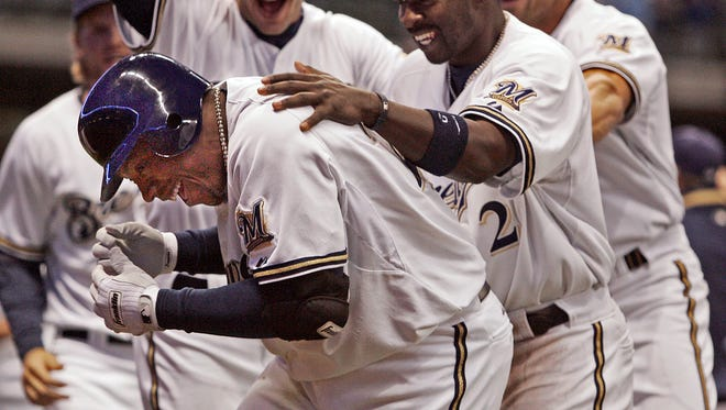 Milwaukee Brewers second baseman Rickie Weeks is mobbed by teammates after delivering the game-winning hit in the 10th inning of a 3-2 win over the Reds on April 8, 2008.