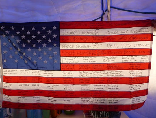 A U.S. flag bearing the names of fallen soldiers carried