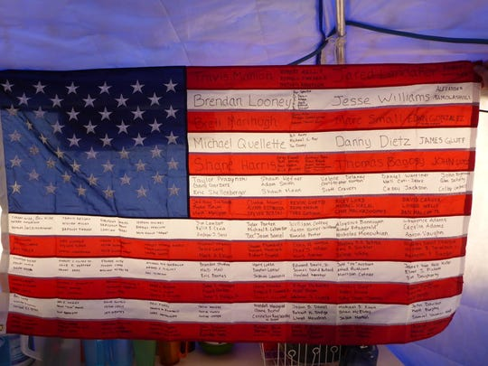 A U.S. flag bearing the names of fallen soldiers carried by members of Mission Memorial Day.