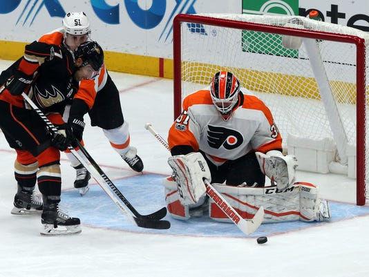 Philadelphia Flyers goalie Brian Elliott (37) guards the goal as Anaheim Ducks left winger Andrew Cogliano (7) presses in the first period of an NHL hockey game in Anaheim, Calif., Saturday, Oct. 7, 2017. (AP Photo/Reed Saxon)