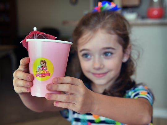 Aleese Haile, 8, displays her copyrighted logo with her likeness that she uses for her lemonade stand business in Wichita Falls, Texas.
