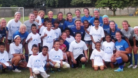 Thomas More soccer team with Costa Rican kids in 2014.