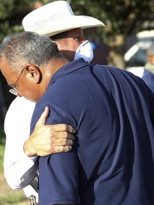 McAllen Police Chief Victor Rodriguez, foreground, is hugged by a Texas Ranger after speaking at a news conference near the scene of a shooting where two of his officers were shot and killed reportedly responding to a disturbance call, Saturday, July 11, 2020, in McAllen, Texas.