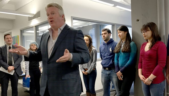 LLamasoft CEO Don Hicks, flanked by several immigrant employees who are pursuing visas, discusses his objections to U.S. immigration policy at the company's office in Ann Arbor on April 9, 2015.