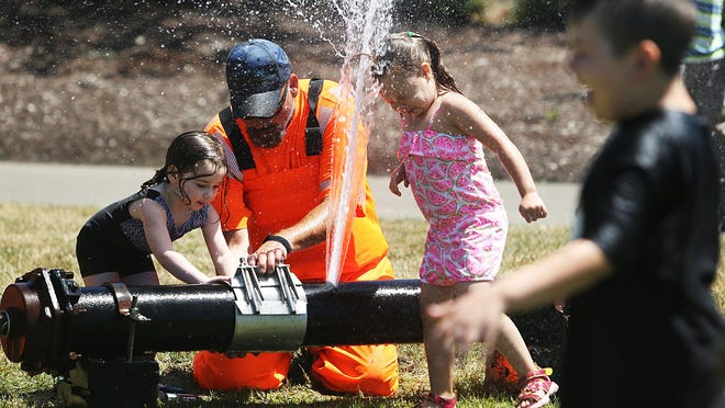 Craig Lynch, of Public Works Water Services, teaches Evie Watson, 2, to repair broken water pipe as Chevelle Stegall, 5, puts her head in the water at the 11th annual Public Works Day celebration at Salem's Riverfront Park Thursday June 19, 2014.