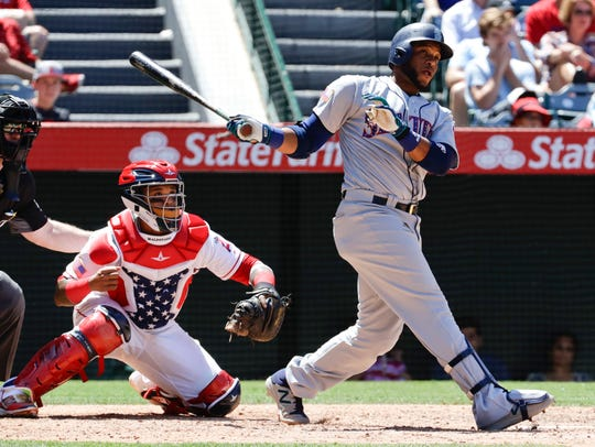Seattle Mariners' Robinson Cano, right, watches his