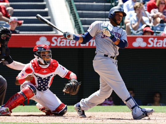 Seattle Mariners' Robinson Cano, right, watches his three-run home run during the eighth inning of a baseball game against the Los Angeles Angels in Anaheim, Calif., Sunday, July 2, 2017. (AP Photo/Chris Carlson)