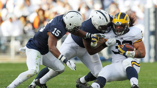 Nov 21, 2015; University Park, PA, USA; Michigan Wolverines fullback Sione Houma (39) runs with the ball as Penn State Nittany Lions cornerback Grant Haley (15) and linebacker Jason Cabinda (40) block during the third quarter at Beaver Stadium. Michigan defeated Penn State 28-16.