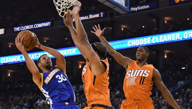November 13, 2016: Golden State Warriors guard Stephen Curry (30) shoots the ball against Phoenix Suns forward Jared Dudley (3) and guard Brandon Knight (11) during the first quarter at Oracle Arena.