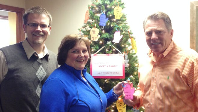 """Wink Chiropractic continues their 30-year tradition of generosity to The Salvation Army. Dr. Scott Suprenand, left, Karen Mengel and Dr. Craig Wink coordinate the office tree that offers clients the opportunity to help provide Christmas for two families """"adopted"""" through The Salvation Army."""
