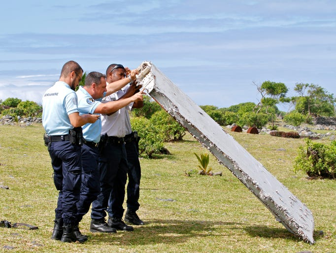 French police officers inspect a piece of debris from