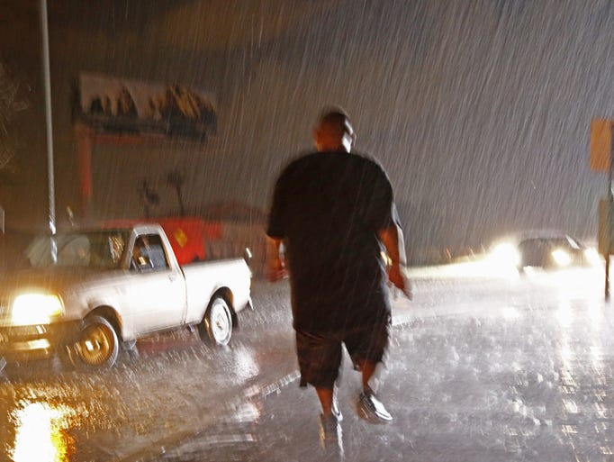 Tow truck owner Gabriel Ortiz runs to help a stranded