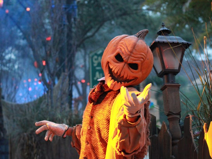 A pumpkin-headed scareactor welcomes guests into the