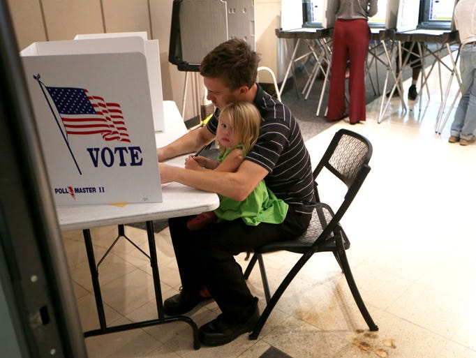 Jordan Johnson casts his vote with his daughter Cadence