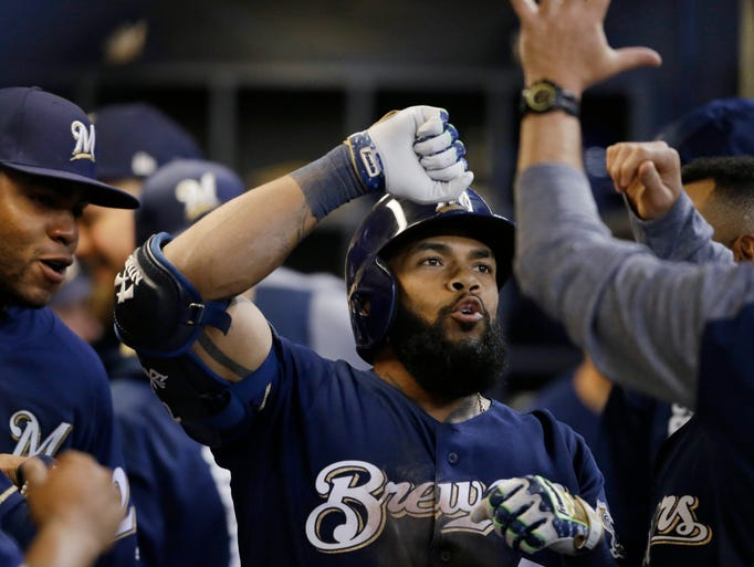 Eric Thames gets high-fives in the dugout after his