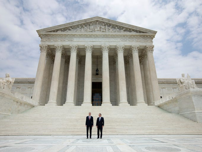 Gorsuch and Chief Justice John Roberts stand together