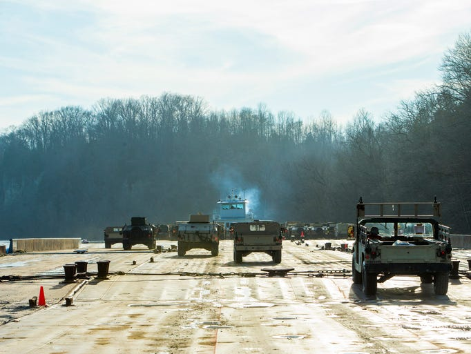 Soldiers drive vehicles onto the barge on February