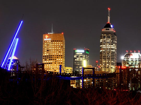 The Indianapolis skyline is seen behind the Beacon of Hope, left, that was lit by the Indianapolis Zoo, on Thursday, March 13, 2014.