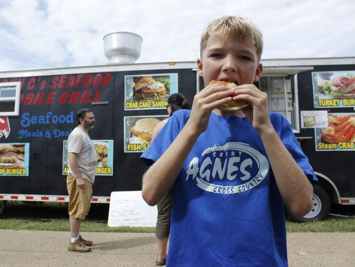Nolan Crider, 8, tries the alligator burger for the