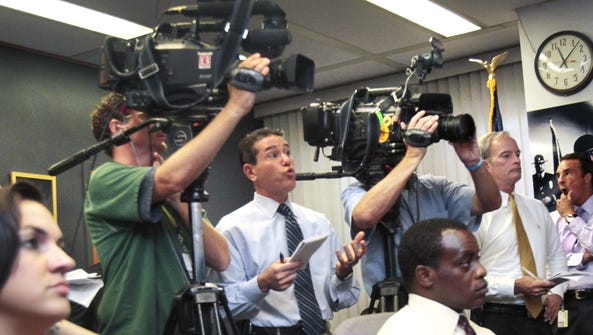 WTHR-13 reporter Jeremy Brilliant (center) asks a questions