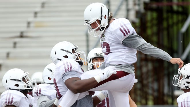 Gold offensive lineman Jeff Savage lifts quarterback Garrett Smith into the air to celebrate a touchdown during the ULM Maroon and Gold Spring Game at JPS Field at Malone Stadium on Saturday. Smith completed 11 of 25 passes for 178 yards with one touchdown and one interception.