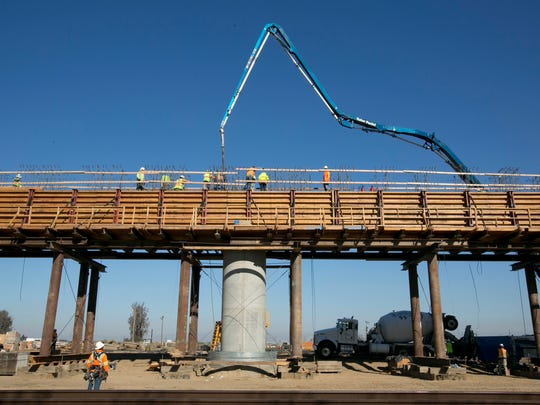 In this Dec. 6, 2017, file, workers pour concrete on to one of the elevated sections of the high-speed rail that will cross over the San Joaquin River, near Fresno. California California's high-speed rail board has approved a 2018 business plan that outlines the challenges in completing the ambitious project to build a bullet train between Los Angeles and San Francisco by 2033.