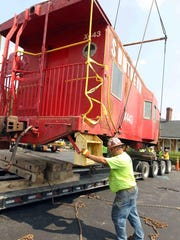 Ernie Begley of Maxim Crane Co. guides a caboose onto a flatbed truck for transport from Depot Park in Erlanger to Progress Rail Services in Taylor Mill for restoration. Progress Rail is doing the approximately $60,000 renovation free of charge.
