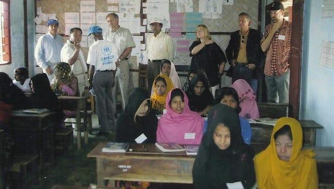 Ron McMullen (in doorway) visits a U.N. literacy program for Rohingya women in Burma in 2003.